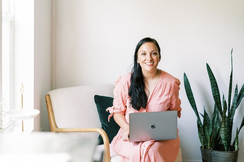 Dolly DeLong Photography is wearing a pink dress and typing in her macbook pro at an airbnb in Nashville