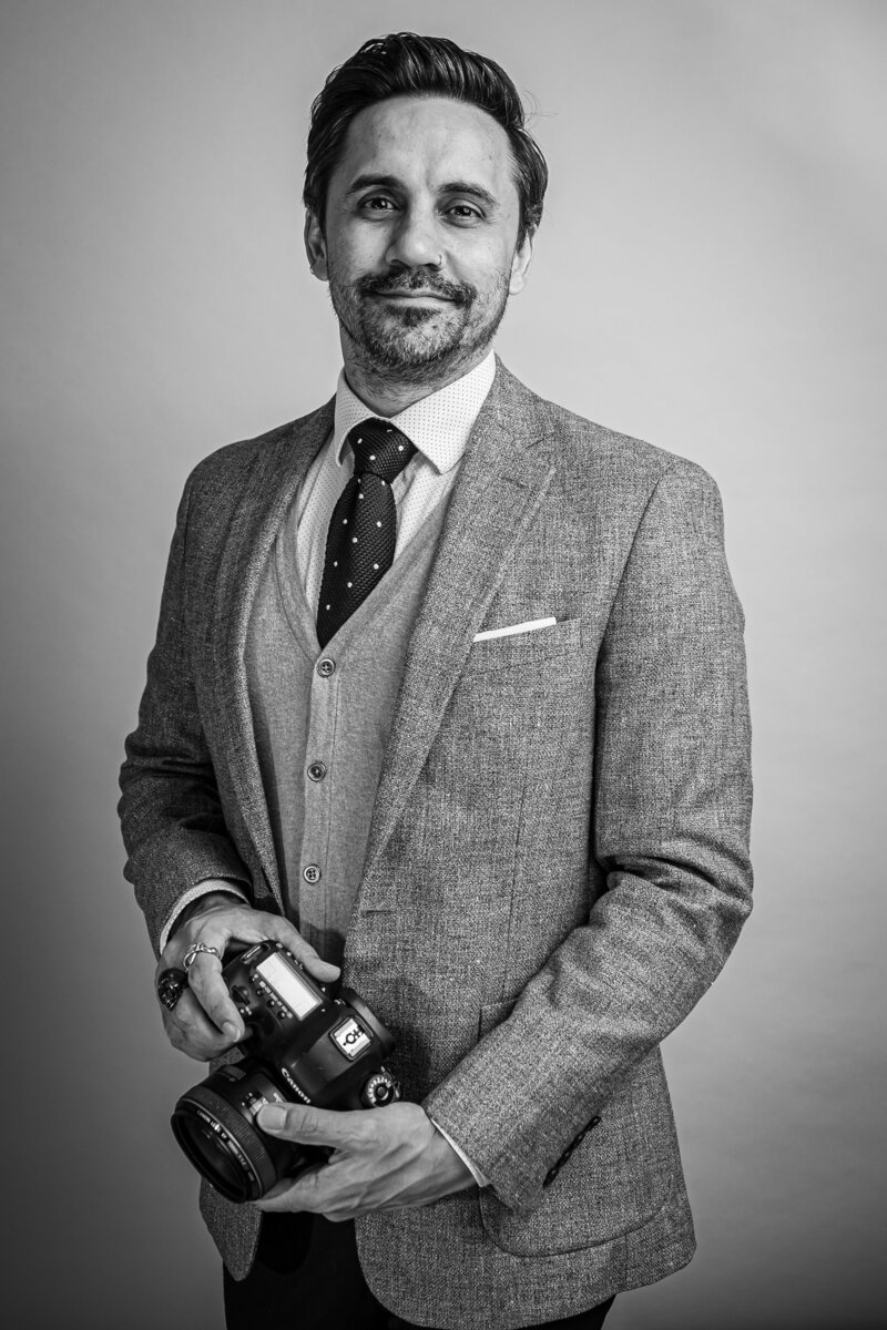 A man in a suit holding a camera