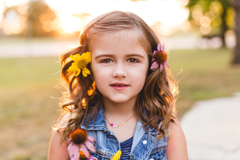golden hour portrait of girl with flowers in her hair family photographer