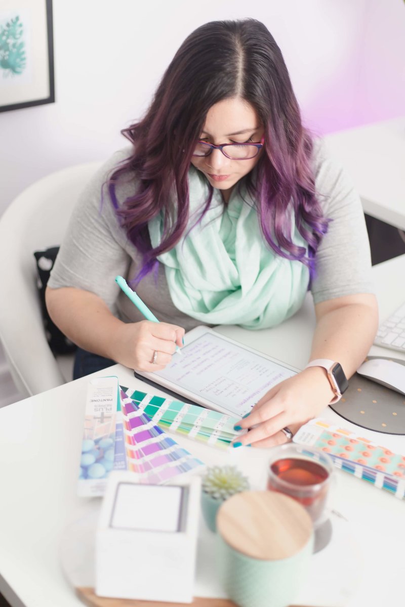 Female designer with purple hair scribbling on an ipad with a teal apple pencil with a desk full of design tools.