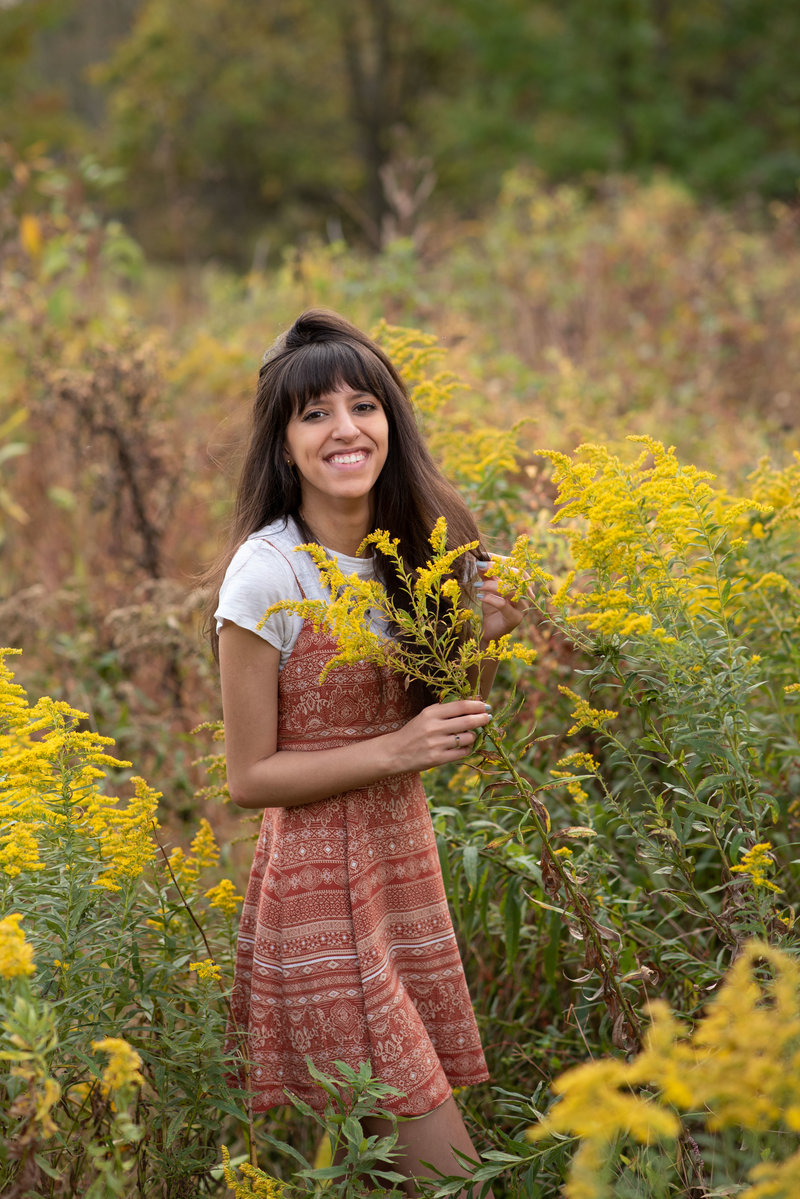 Senior girl in field of golden flowers