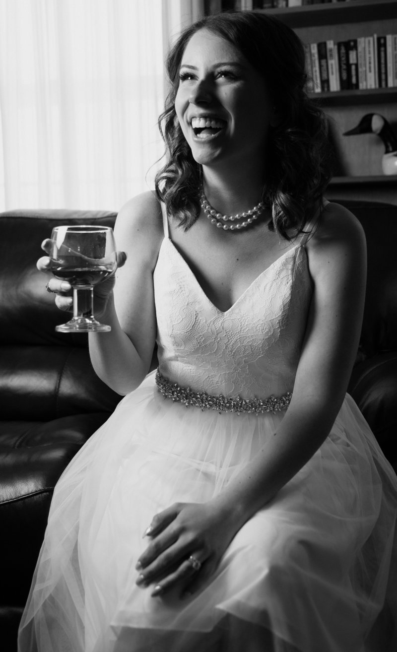 Bride laughs while holding a glass of whiskey during brial portraits at the Barn at Conneaut Creek