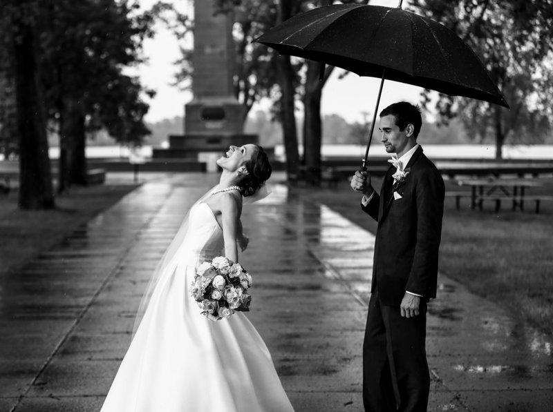 Bride stands in the rain while groom holds umbrella at Presque Isle State Park