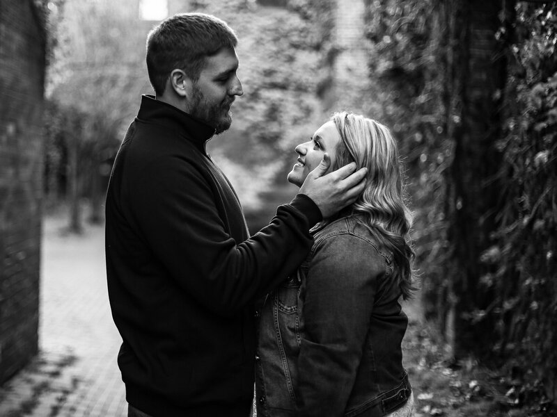 Man caresses fiancee's cheek for engagement photo session at Modern Tool Square in Erie PA