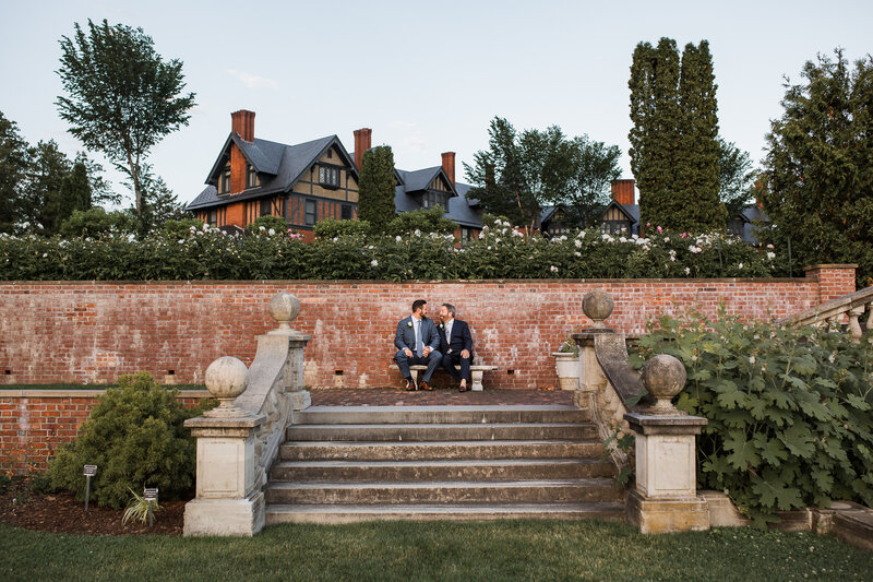 groom and groom sitting on bench smiling at each other and holding hands