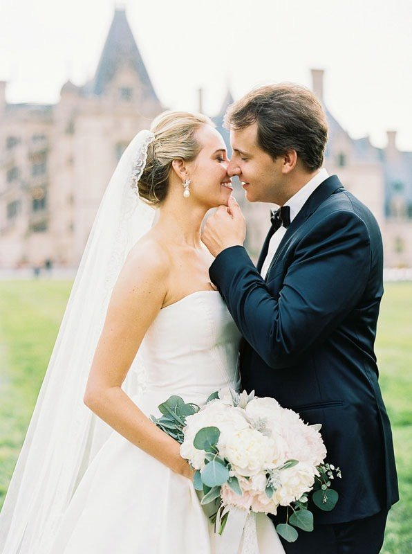 bride and groom kissing in front of venue