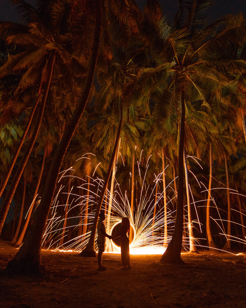 A couple are silhouetted against a catherine wheel on a beach for a wedding proposal in Barbados.