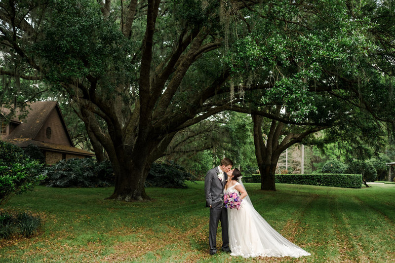 wide angle of couple under huge oak trees at  Club Lake Plantation