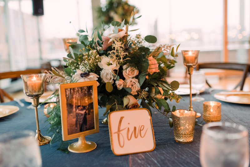 Lush floral centerpiece with gold candles and table numbers