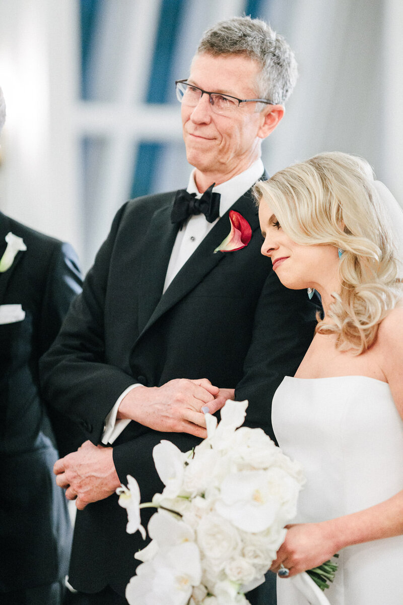 father and daughter at wedding ceremony altar aisle embracing