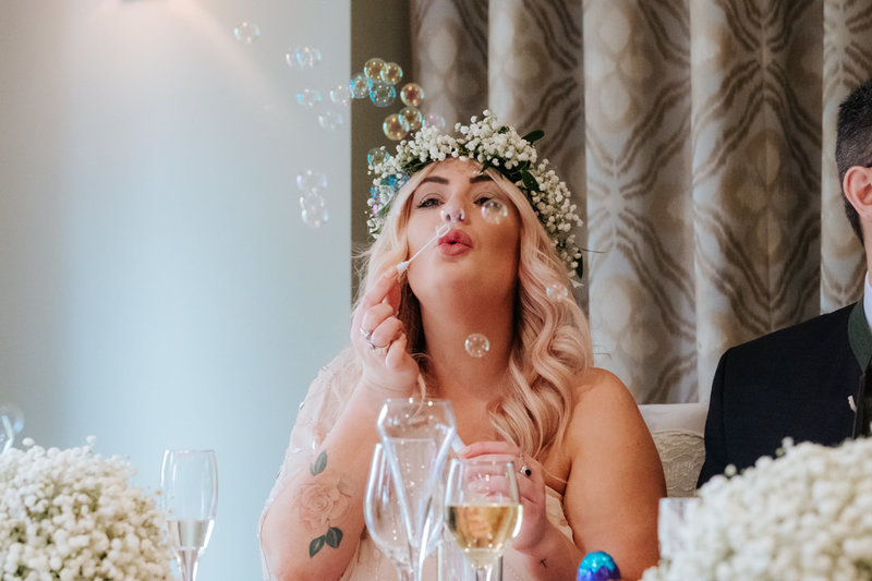 bridesmaid dressed in pink, wearing a large flower crown blows bubbles as she sits at the dinner table at Woodland Grand wedding venue in Kenilworth Warwickshire