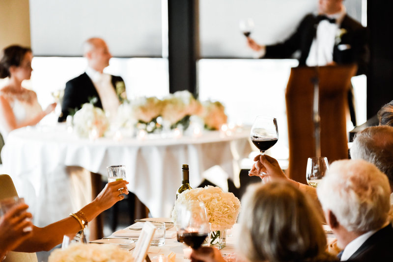 Wine glasses raised at a toast at this Canoe Wedding