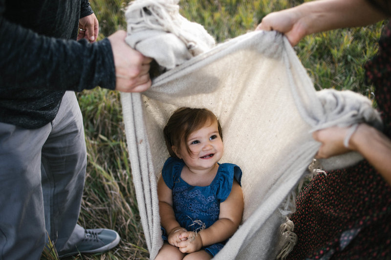 Little girl smiling and swinging in blanket with mom and dad