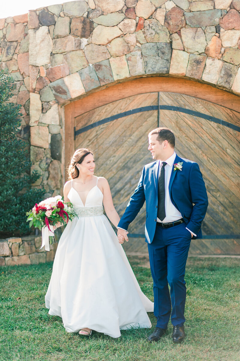 Bride and groom holding hands in front of wooden doors at Stone Tower.