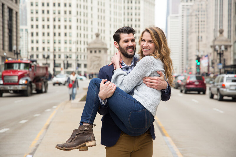couple on michigan avenue kissing after surprise proposal in downtown chicago