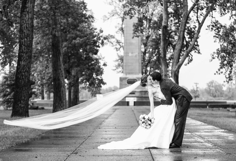 Bride and groom kiss as winds lift the veil at Perry Monument on Presque Isle State Park