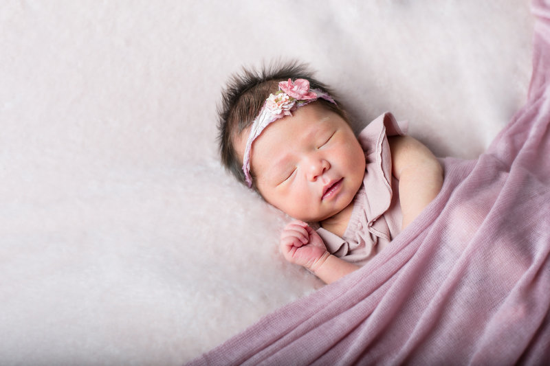 Newborn baby girl posing for portrait in Denver photography studio