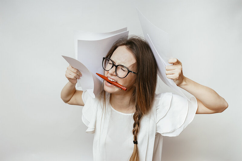 woman frustrated with paperwork biting pen