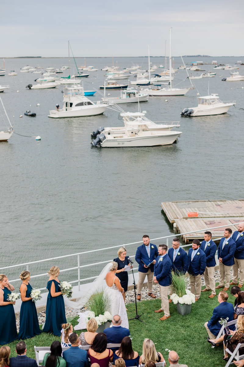 A wedding ceremony takes place with boats in the harbor in the distance at Duxbury Bay Maritime School