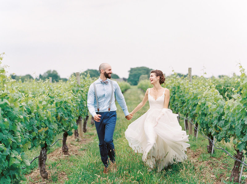 Laura Volpacchio and David Simon run through the vines at Wolffer Estate Vineyards at their wedding on June 29, 2019.