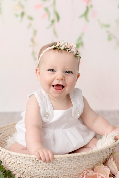 baby girl smiles against a light pink floral background