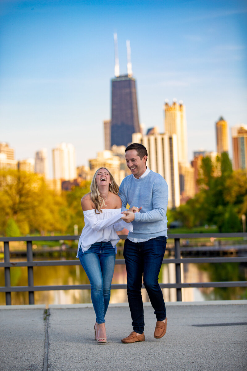 A groom makes his bride laugh during their fall engagement session with downtown Chicago in the background.