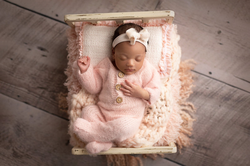 columbus-ohio-newborn-photographer-baby-girl-in-pink-on-baby-bed-amanda-estep-photography
