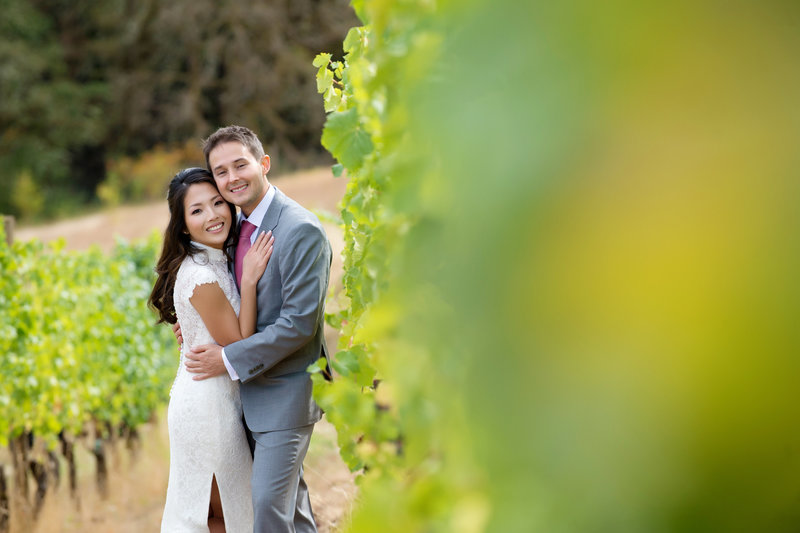a bride and groom pose among the grapevines at youngberg hill after their wedding