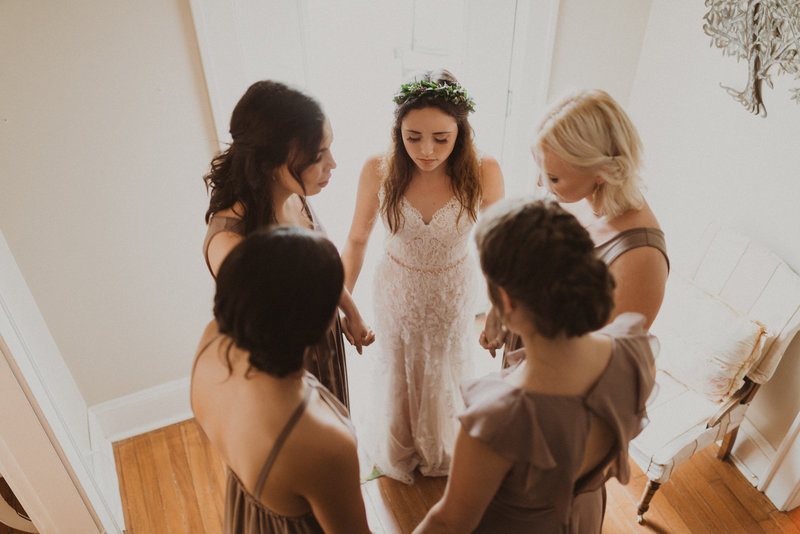 Wedding bridal party prays for bride