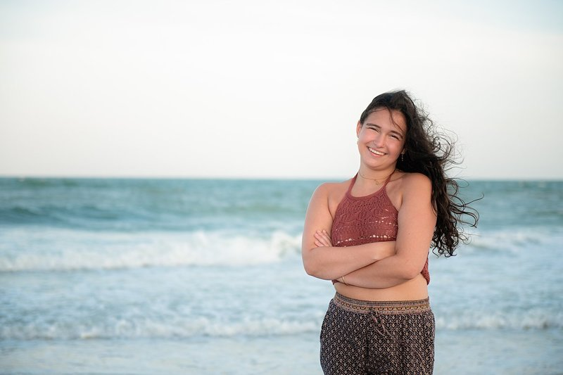 High school senior girl wearing harem pants and rust crocheted crop top standing with arms crossed on windy beach with waves crashing in background