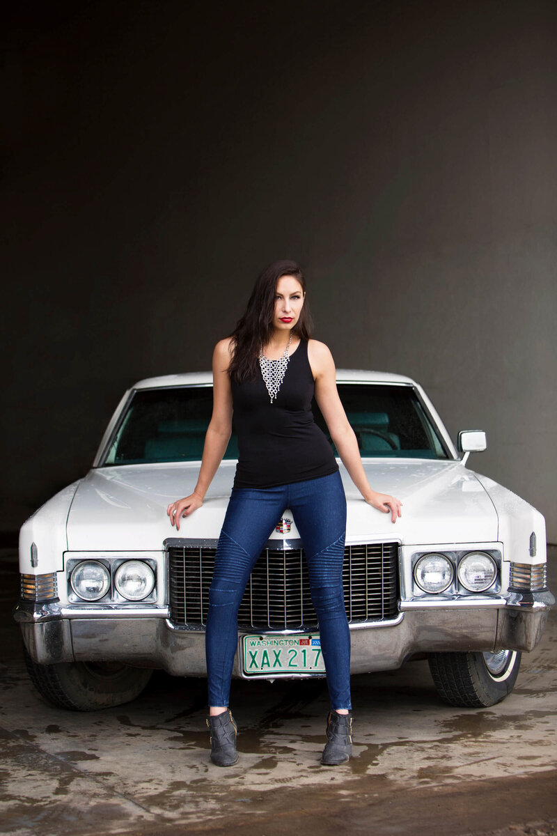 model leaning on  hood of vintage cadillac