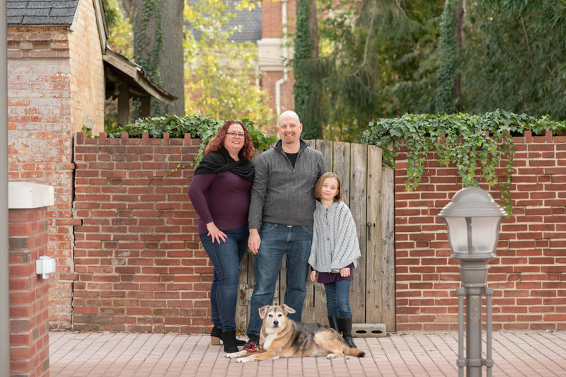 Family of 3 with their dog in front of an ivy covered brick wall with a wooden gate