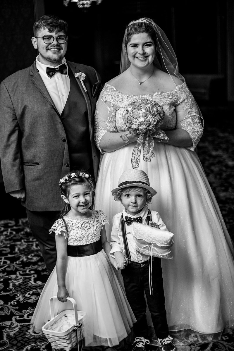 Bride and groom pose with flower girl and ring bearer at the Warner Theatre