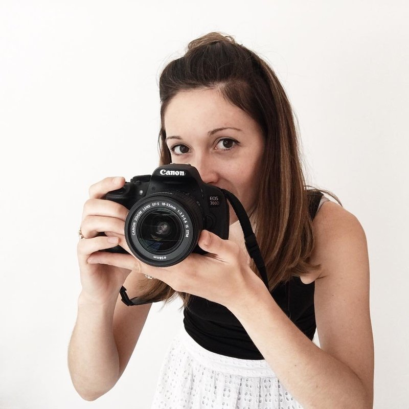 Woman holding a camera and smiling