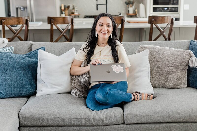 Dolly of Dolly DeLong Photography A Nashville Branding Photographer and Nashville Family Photographer is sitting on a giant couch and checking her email on her apple macbook for her branding photos
