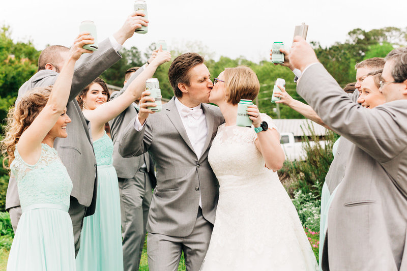 wedding party toasts and celebrates around the bride and groom kissing