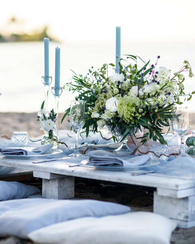 A table with light blue candles and flowers set up on luxury boho table on the beach.