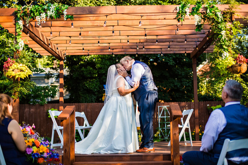 First kiss as husband and wife at  intimate garden wedding ceremony in Erie, PA