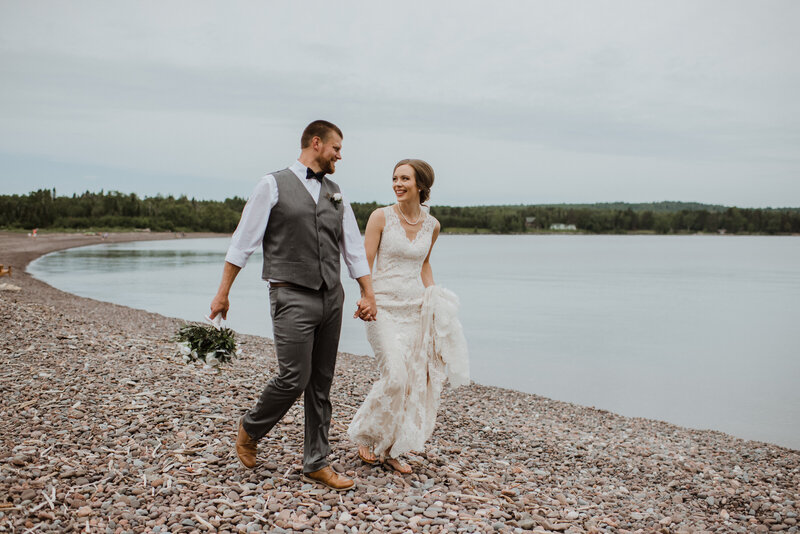 Bride and groom walking outdoors by the lake