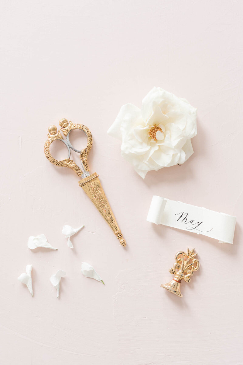 A lay flat of luxurious trinkets and soft flowers