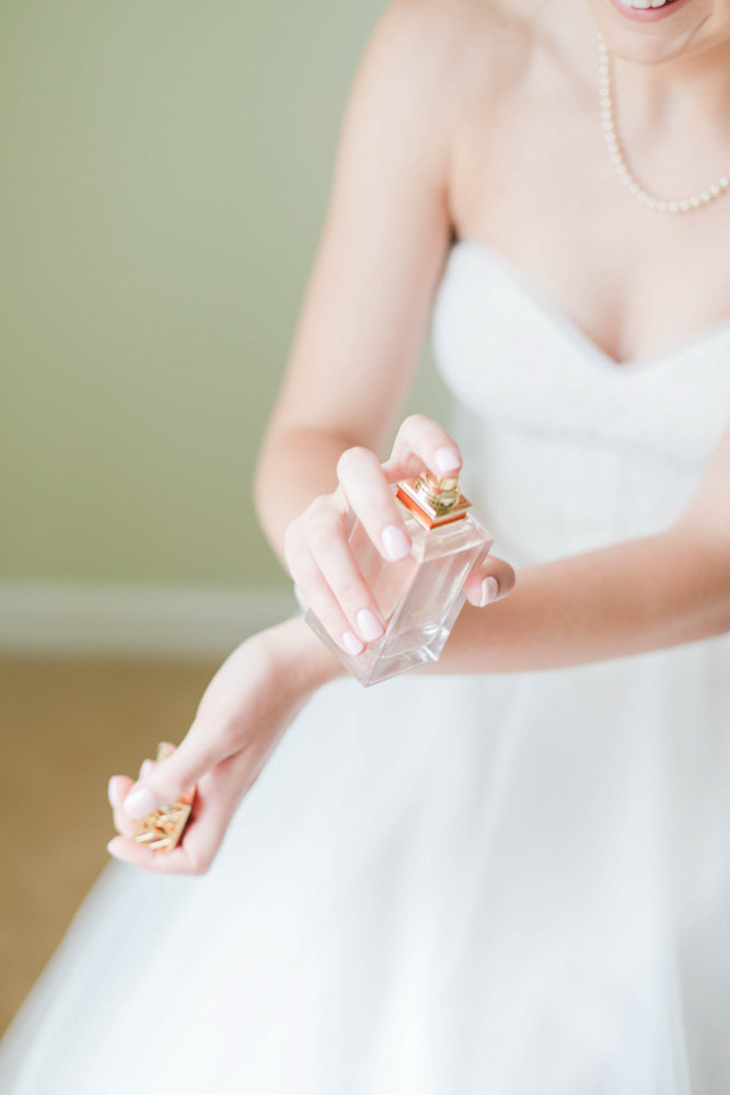 bride putting on tory burch perfume at eastern shore wedding at kirkland manor by costola photography