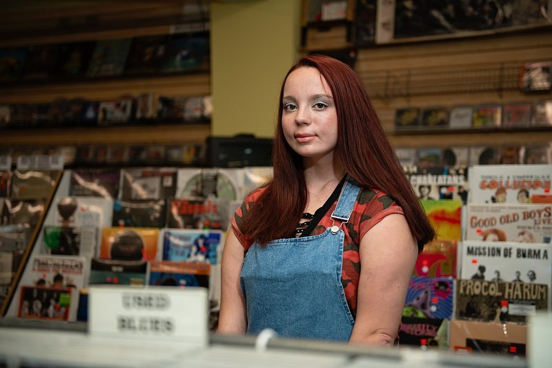 High school senior girl with jean overalls and red camo tee standing among the stacks at Eide's record store in Pittsburgh, PA