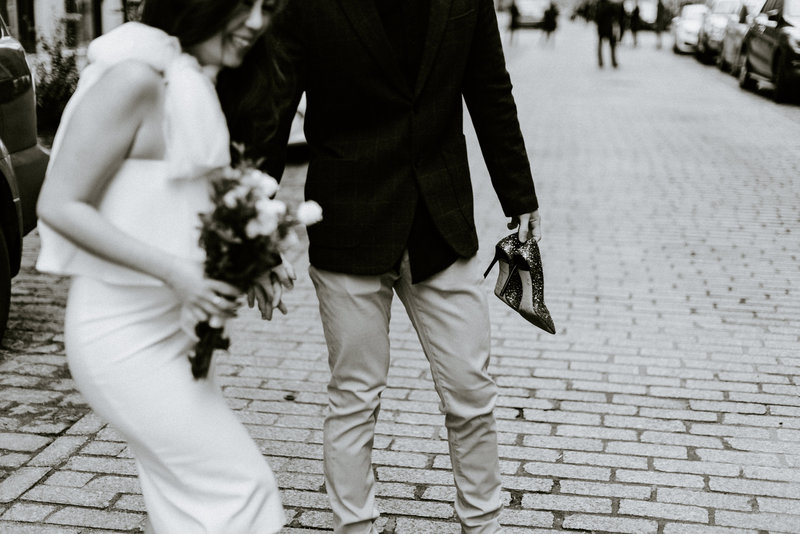 black and white photo out of focus and off crop of the girl holding a bouquet while her fiance holds her other hand
