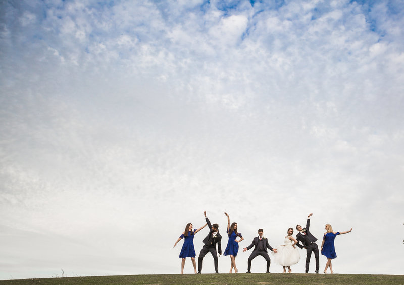 A bride and groom and their wedding party strike a fun pose against a big blue sky at haughley park bard wedding venue suffolk.