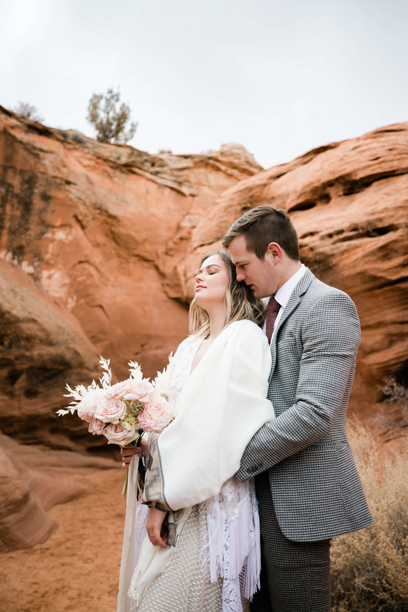 the groom hugs his bride close at the opening of a desert slot canyon