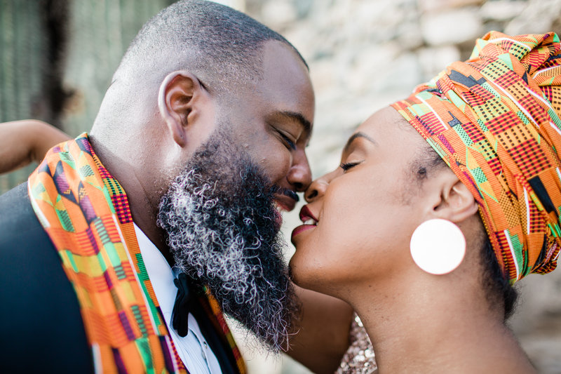 an adventurous couple leans in to kiss. the bride and groom both wear a kente cloth
