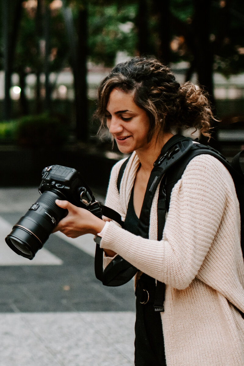 woman holding camera while smiling