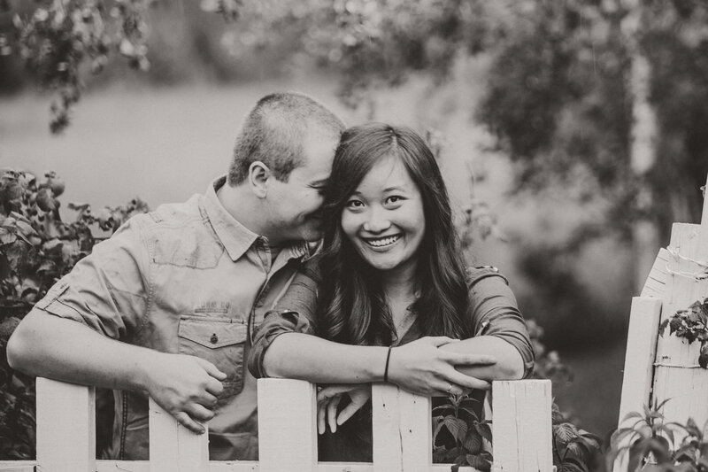 engaged couple leans on picket fence