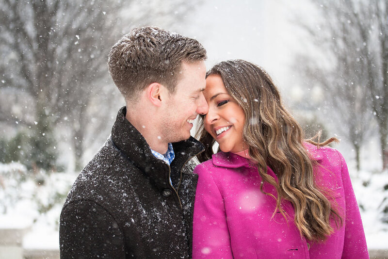 couple kiss during downtown detroit snowy winter engagement session