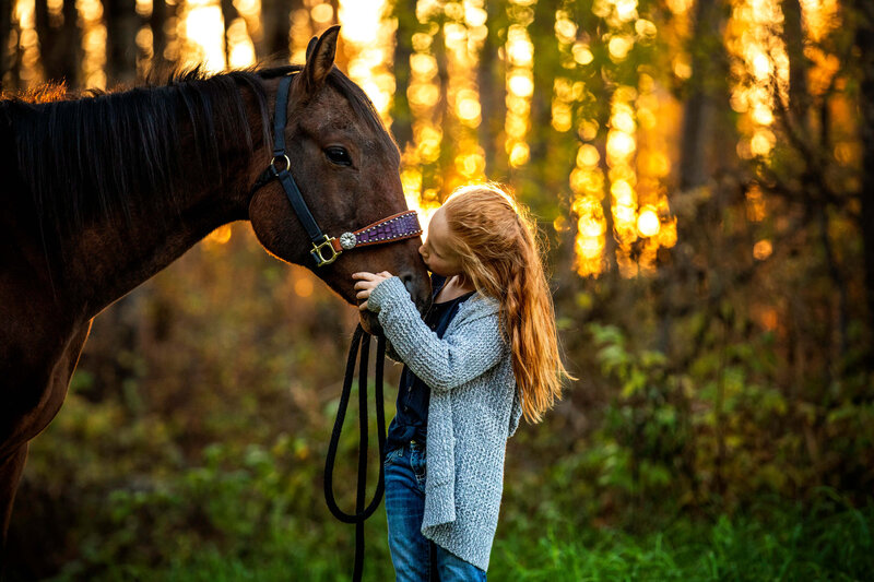 little girl with red hair kissing her horse